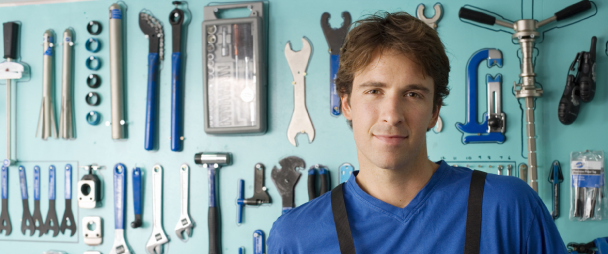 mechanic with wall of tools